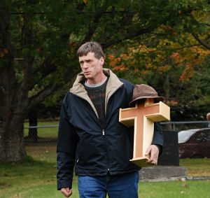 Mike Holm carrying his father's urn into the cemetery