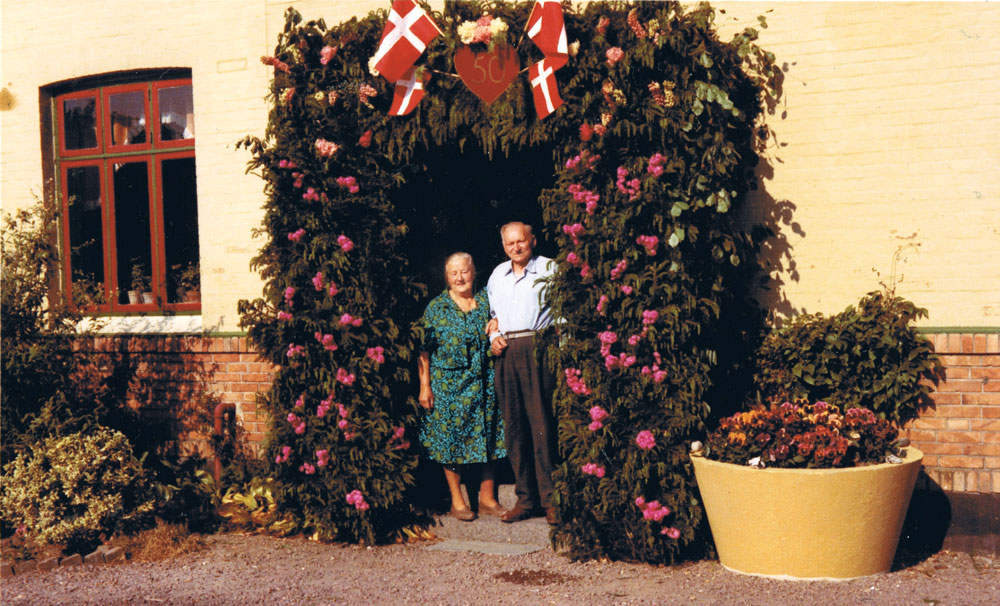 "Johannes and Ellen celebrating their 50th wedding anniversary, standing under the traditional ""gate of honour"" erected by their family."